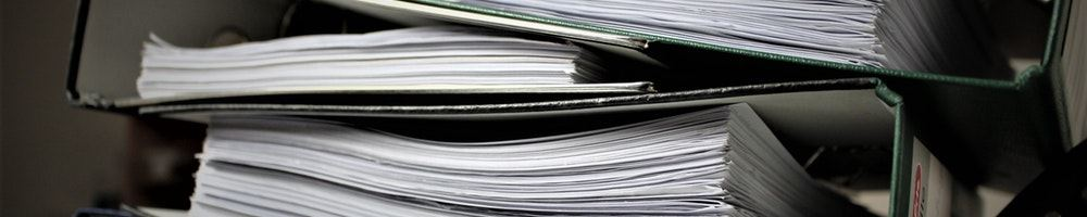 Side view of a stack of binders full of white paper.