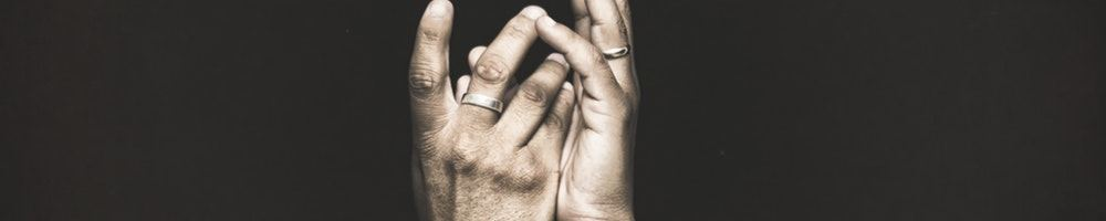 Two hands touching with fingers pointing up on a black background.
